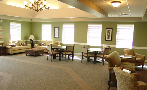 Stoney Brook Memory Care Living And Dining Room With Green Accent Walls  With Custom Upholstery Pieces